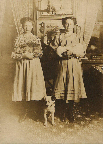Two girls with rabbits and dog